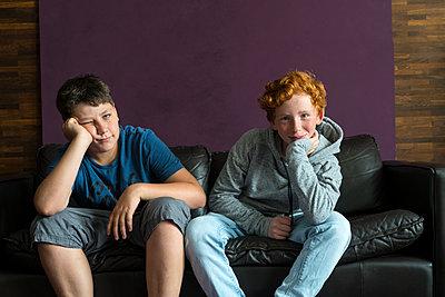 Mädchen und Junge sitzen auf dem Sofa - p427m1465446 von R. Mohr