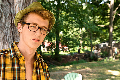 Young man wearing eyeglasses and fedora - p924m734336f by Dreampictures