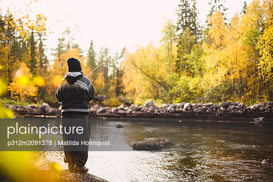 Woman fishing in river - p312m2091378 by Matilda Holmqvist