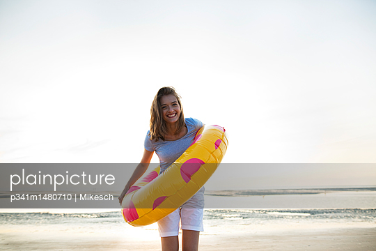 Young woman with colourful swimming ring  - p341m1480710 by Mikesch