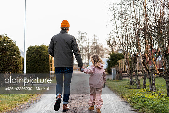 Full length rear of view father and daughter holding hands while walking on road - p426m2296230 by Maskot