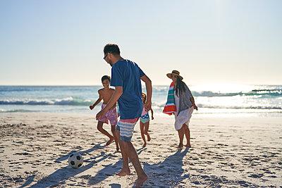Family playing soccer on sunny ocean beach - p1023m2200882 by Trevor Adeline