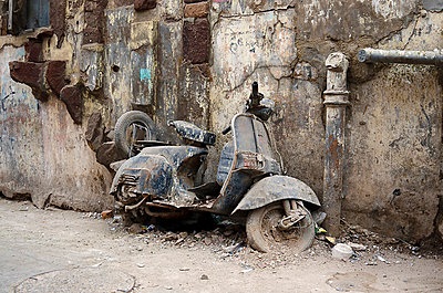 Defunct motorscooter leaning against derelict city wall - p1072m941367 by chinch gryniewicz