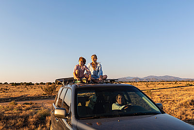 Teenage girl and her younger brother  on top of SUV on desert road - p1100m2220331 by Mint Images