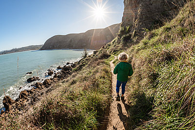 Preschooler walking on seaside mountain path on sunny day in New Zealand - p1166m2177015 by Cavan Images