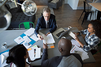 Financial advisor with laptop and paperwork meeting with family at dining room table - p1192m1201896 by Hero Images