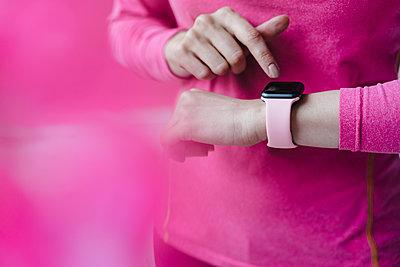 Close-up of woman in pink sportswear adjusting her smartwatch - p300m1535737 by Kniel Synnatzschke