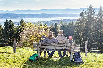 Rear view of family sitting on park bench looking out at view, Tutzing, Bavaria, Germany - p429m1084544 by Ingolf Hatz