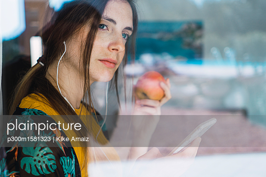Young woman with earphones, cell phone and apple looking out of window - p300m1581323 von Kike Arnaiz