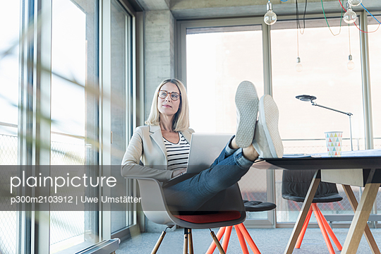 plainpicture - plainpicture p300m2103912 - Relaxed businesswoman using... - DEEPOL by plainpicture/Uwe Umstätter