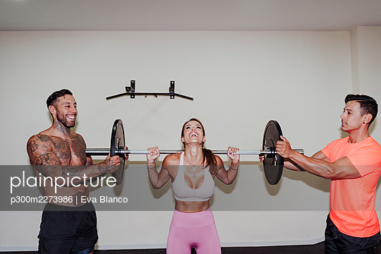 Male athletes helping female friend in exercising with barbell at gym - p300m2273986 by Eva Blanco