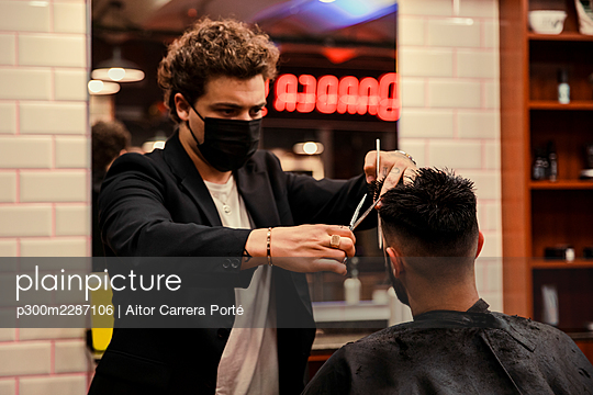 Stylish barber with mask cutting hair with scissors and a comb to a young guy in his barbershop. - p300m2287106 von Aitor Carrera Porté