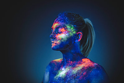 Conceptual shot of light and shine fluorescent colors young girl's fac - p1166m2096317 by Cavan Images