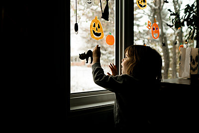 Young girl putting Halloween decorations up on windows in living room - p1166m2268987 by Cavan Images