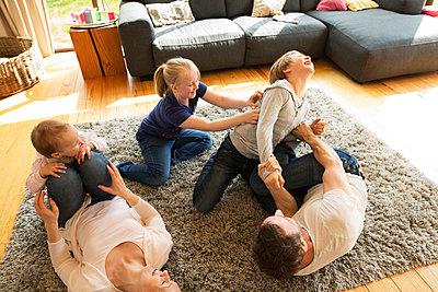 Familie im Wohnzimmer spielt zusammen - p341m1137190 von Mikesch