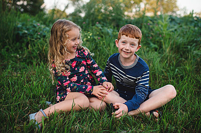 Girl and brother sitting in field - p429m1504625 by Erin Lester