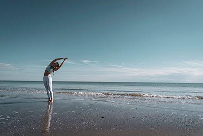 Woman practising yoga on beach - p429m2019415 by Ingolf Hatz
