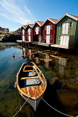 Fishing huts reflecting in harbor - p575m718482f by Benny Karlsson