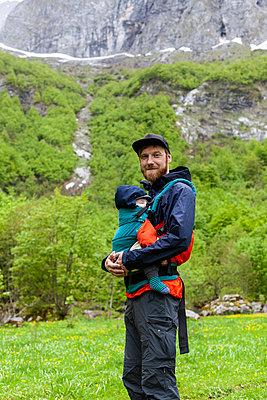 Vater wandert mit Baby auf dem Arm durch die Berge - p795m2158217 von JanJasperKlein