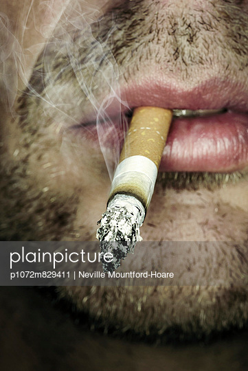 Close-up of man smoking a cigarette  - p1072m829411 by Neville Mountford-Hoare