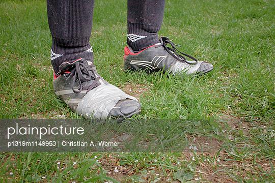Mit Klebeband geflickter Schuh eines Amateurfußballers - p1319m1149953 von Christian A. Werner