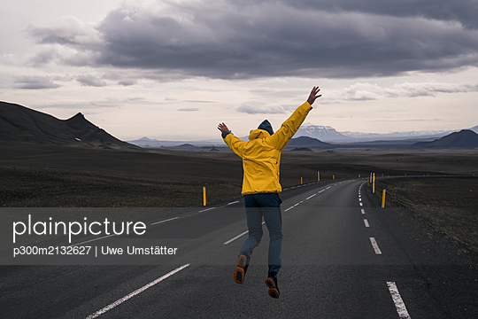 Happy man jumping for joy on an empty road, Iceland - p300m2132627 by Uwe Umstätter
