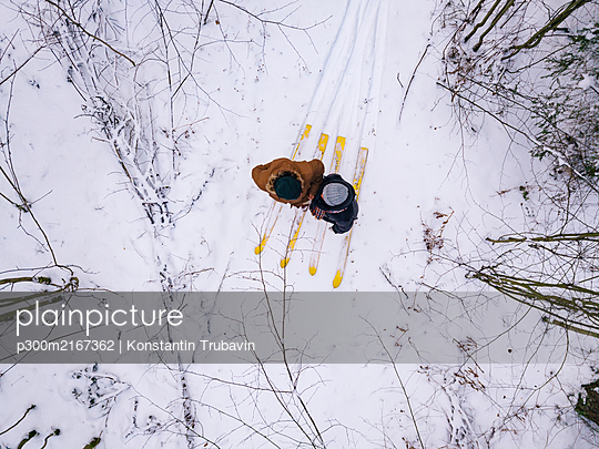 Aerial view of couple with skis in the forest, Leningrad region, Russia - p300m2167362 by Konstantin Trubavin