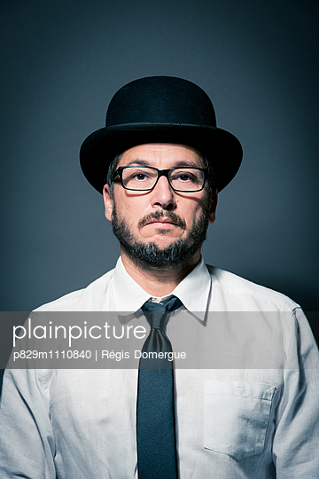 Portrait of man with eyeglasses and hat - p829m1110840 by Régis Domergue