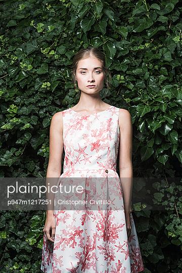 Junge Frau mit geblümtem Kleid - p947m1217251 von Cristopher Civitillo