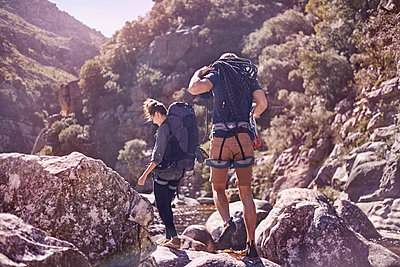 Young couple with backpacks hiking over sunny rocks - p1023m1226633 by Trevor Adeline