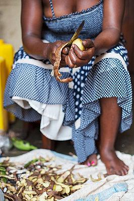 Africa, Uganda, African woman peeling potato - p1167m2283462 by Maria Schiffer