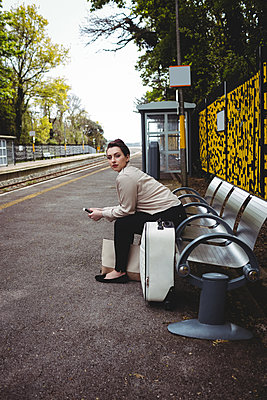 Woman on bench at railroad station platform - p1315m1199951 by Wavebreak