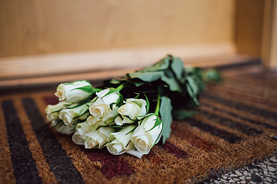 Bunch of white farewell flowers lying on floor mat at apartment door of deceased neighbour - p300m1562596 by Jonathan Schöps