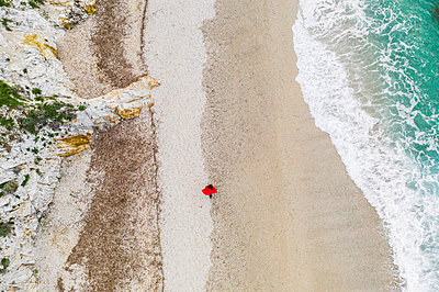 Italy, Elba, woman with red coat walking at beach, aerial view with drone - p300m2069768 by Francesco Buttitta