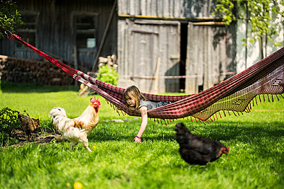Girl relaxing in hammock in garden of a farm with chicken in foreground - p300m2081272 by Steve Brookland