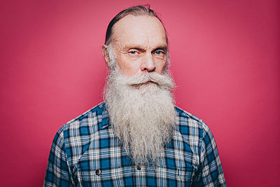 Portrait of serious senior man with long white beard against pink background - p426m1588484 by Maskot