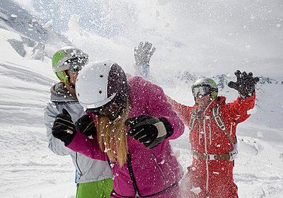 Drei Freunde in Skianzügen machen eine Schneeballschlacht - p4737774f von STOCK4B-RF