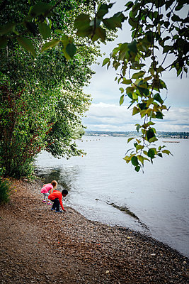 Boy and girl crouching at river - p555m1303899 by Inti St Clair photography