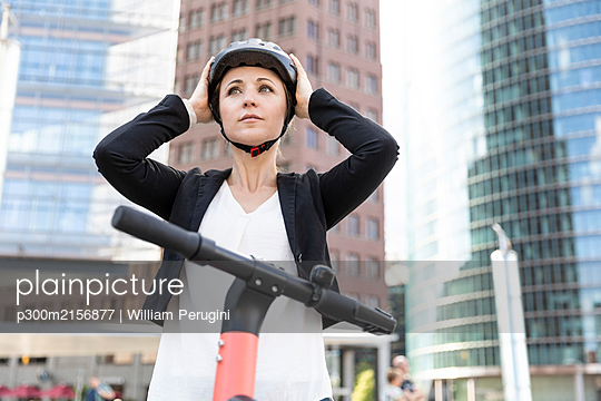 Woman with e-scooter in the city putting on helmet, Berlin, Germany - p300m2156877 by William Perugini