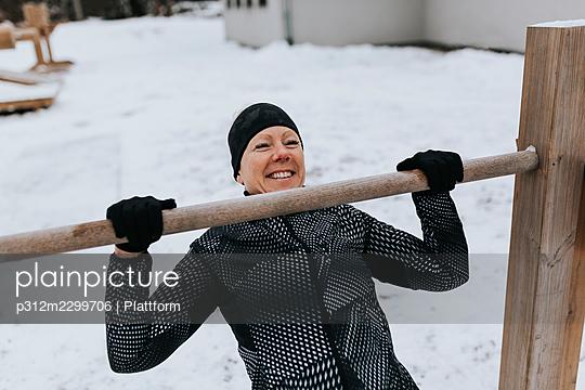Smiling woman exercising at winter - p312m2299706 by Plattform