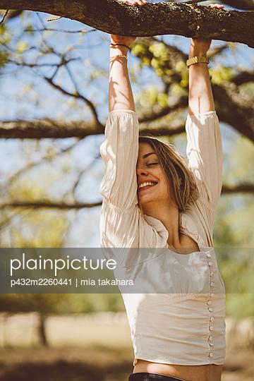 Junge Frau hängt lachend an einem Baum - p432m2260441 von mia takahara