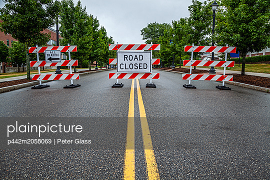 Double yellow line on a street with traffic barriers and 'Road Closed' sign; Connecticut, United States of America - p442m2058069 by Peter Glass