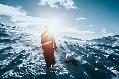 Man walking along sunny snow covered landscape, Reykjadalur, Iceland - p301m2075514 by Sven Hagolani