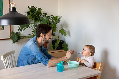 Father feeding baby at table - p312m2190461 by Susanne Kronholm