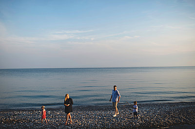 Mid adult parents strolling with boy and girl on pebble beach at Lake Ontario, Oshawa, Canada - p429m1175363 by Erin Lester