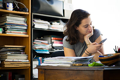 Office worker taking break to browse social media using smartphone - p623m1221274 by Frederic Cirou