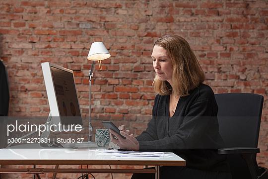 Female entrepreneur using mobile phone at desk in office - p300m2273931 by Studio 27