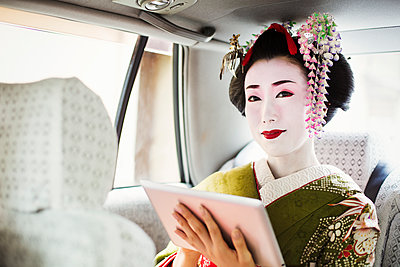 A woman dressed in the traditional geisha style, wearing a kimono with an elaborate hairstyle and floral hair clips, with white face makeup holding a digital tablet, travelling in a car.  - p1100m1185733 by Mint Images