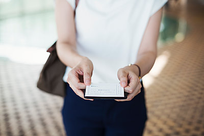 Close up of woman standing in subway station, holding ticket, Tokyo commuter.  - p1100m1531111 by Mint Images