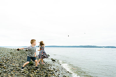 Playful siblings skimming stones in sea while standing at beach against clear sky - p1166m2025797 by Cavan Images